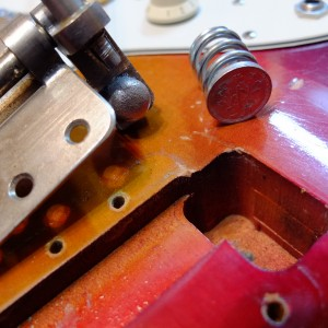 Tremolo out of the cavity with spring removed. One yen coin added for extra stability.